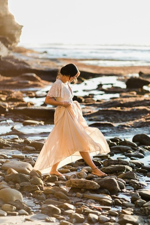 boho bride walking across the rocky beach