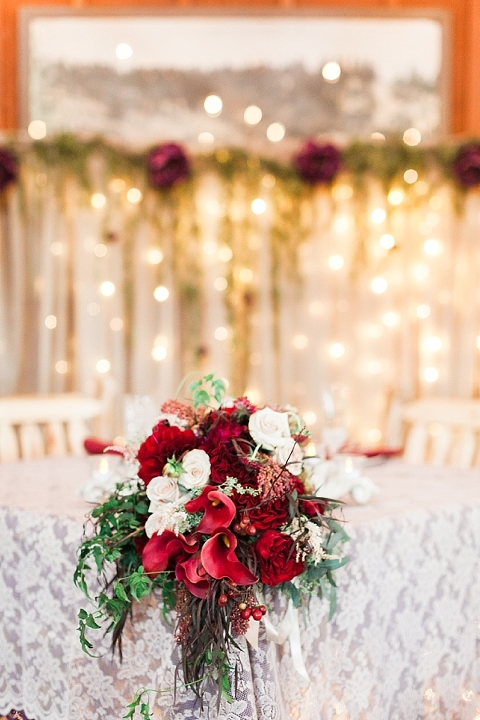 Wedding with dark red florals and twinkle lights