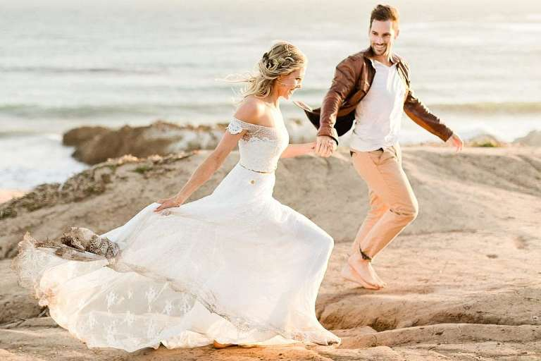 Couple running on Malibu cliffs at sunset for elopement pictures