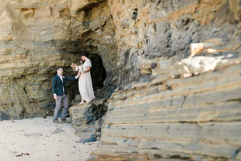 Elopement couple climbing cliffs together in Sunset Cliffs Park