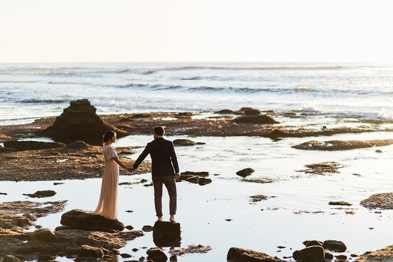 elopement couple walking on the rocky beach