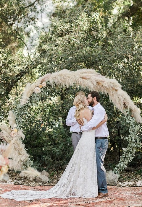 First kiss during boho elopement ceremony in Ojai