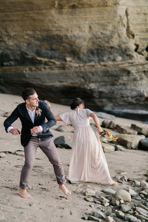 couple skipping rocks at sunset cliffs elopement