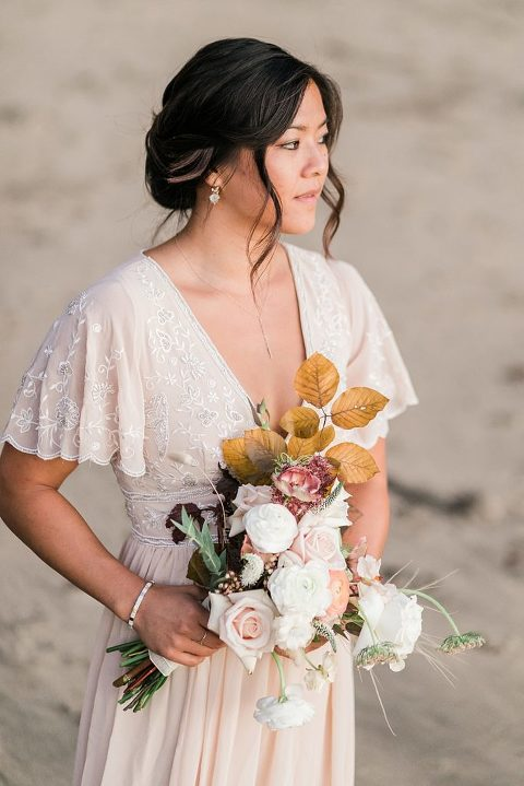 boho bride holding a fall inspired bouquet on the beach