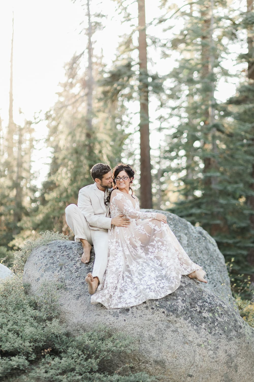 California elopement package information and elopement couple sitting on rock in Yosemite